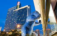 Photo of the blue bear looking into the Colorado Convention Center with the Hyatt Regency hotel behind the bear.