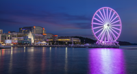 Evening view of the Capital Wheel bathed in purple light at National Harbor, MD