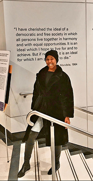 Tavia Record. She is standing on steps to the Nelson Mandela Art Show in front of a marble slab with a 1964 quote by Nelson Mandela. She is wearing a black cap, black coat, black over-the-knee boots, dark gray top, and light gray pants.