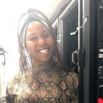 Photo of Tavia Record stand-ing next to computer racks. She is wearing dreadlocks with a gray headband, a snakeskin-print blouse, and a black skirt.